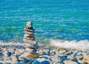 tower of small stones balanced one on another on a rocky shore with the ocean in the background