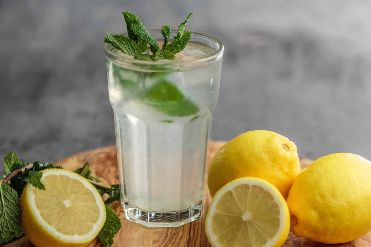 glass of lemonade with mint on a wood cutting board with lemons around it