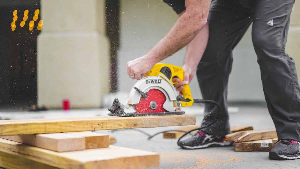 man using a circular saw to cut lumber on the floor