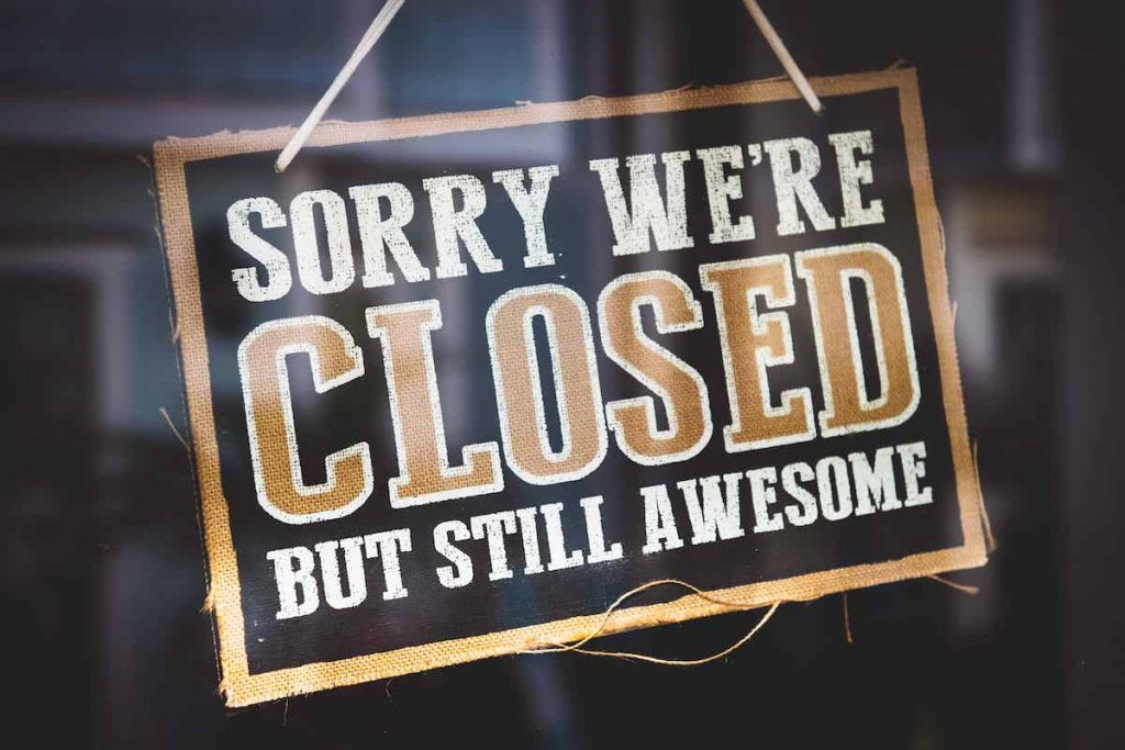 "sign hanging in store front reading ""sorry we're closed but still awesome"""