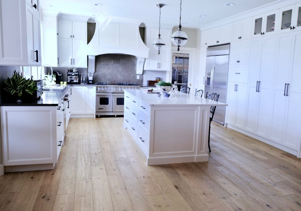 White kitchen with light oak floors featuring an island with storage and seating