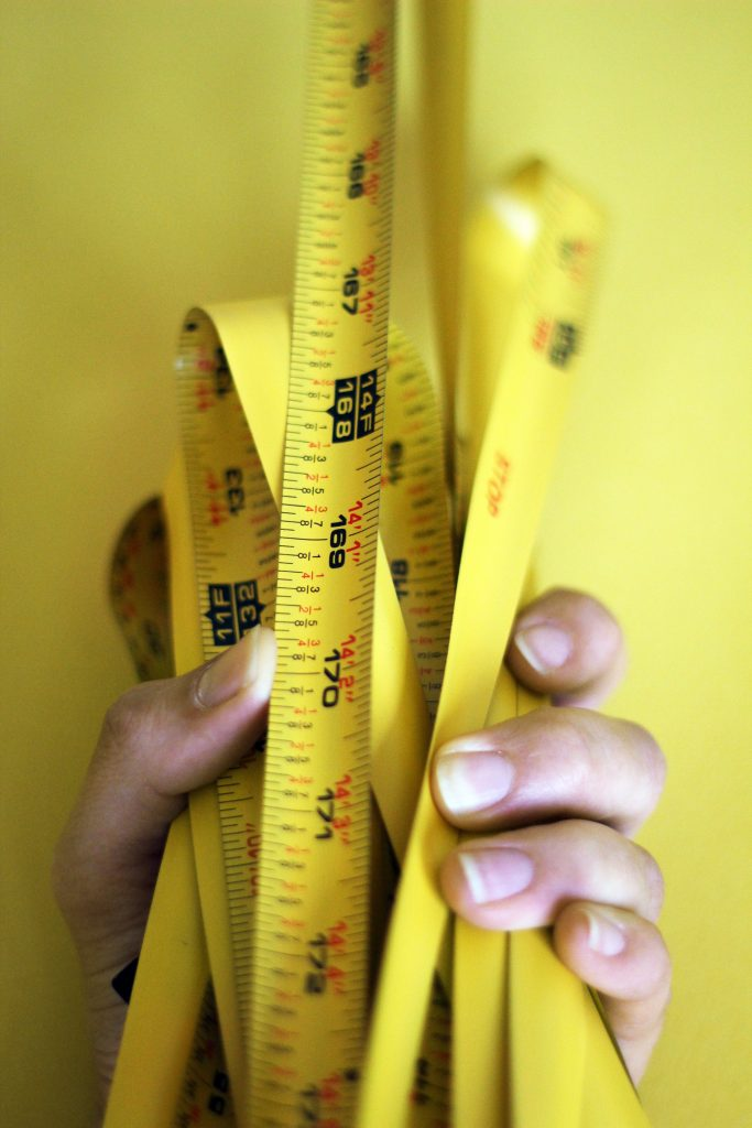 hand clutching measuring tape